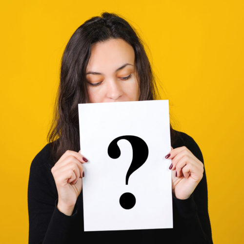 Question mark, symbol. Cute girl holding a question mark over yellow background. Card with question mark symbol. Women questions. Getting answers, thinking.
